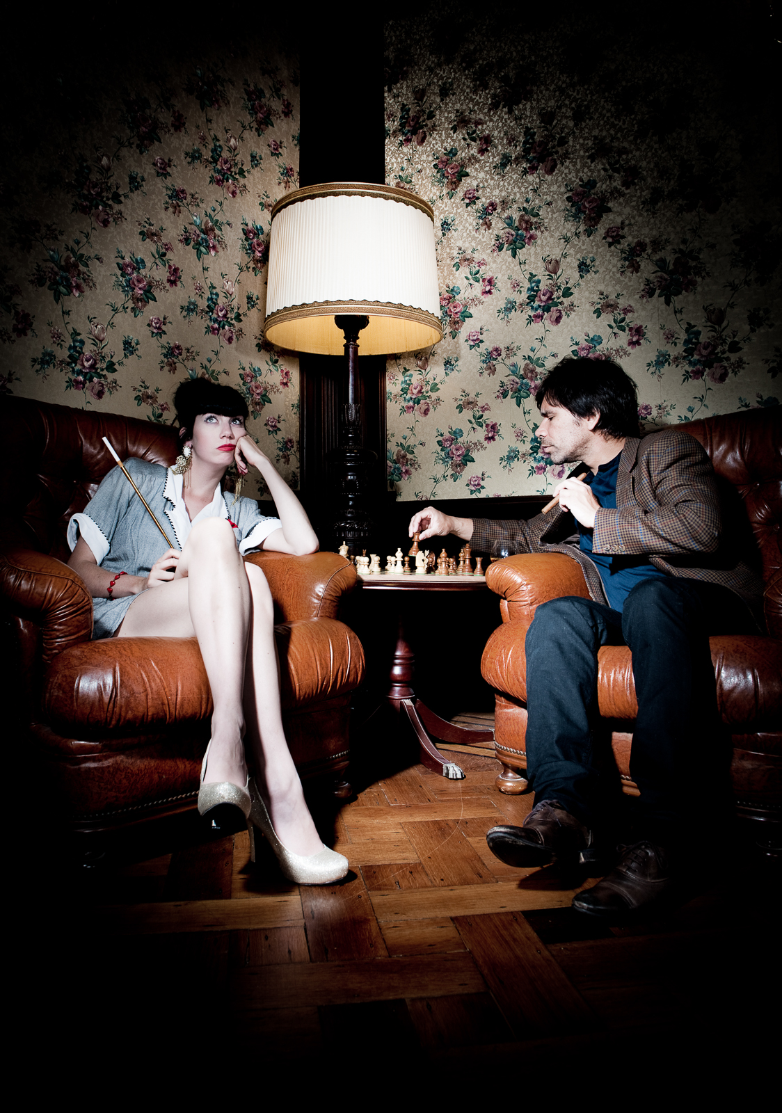 Two people, a man and a woman, sitting in chesterfields playing a game of chess to kill time.