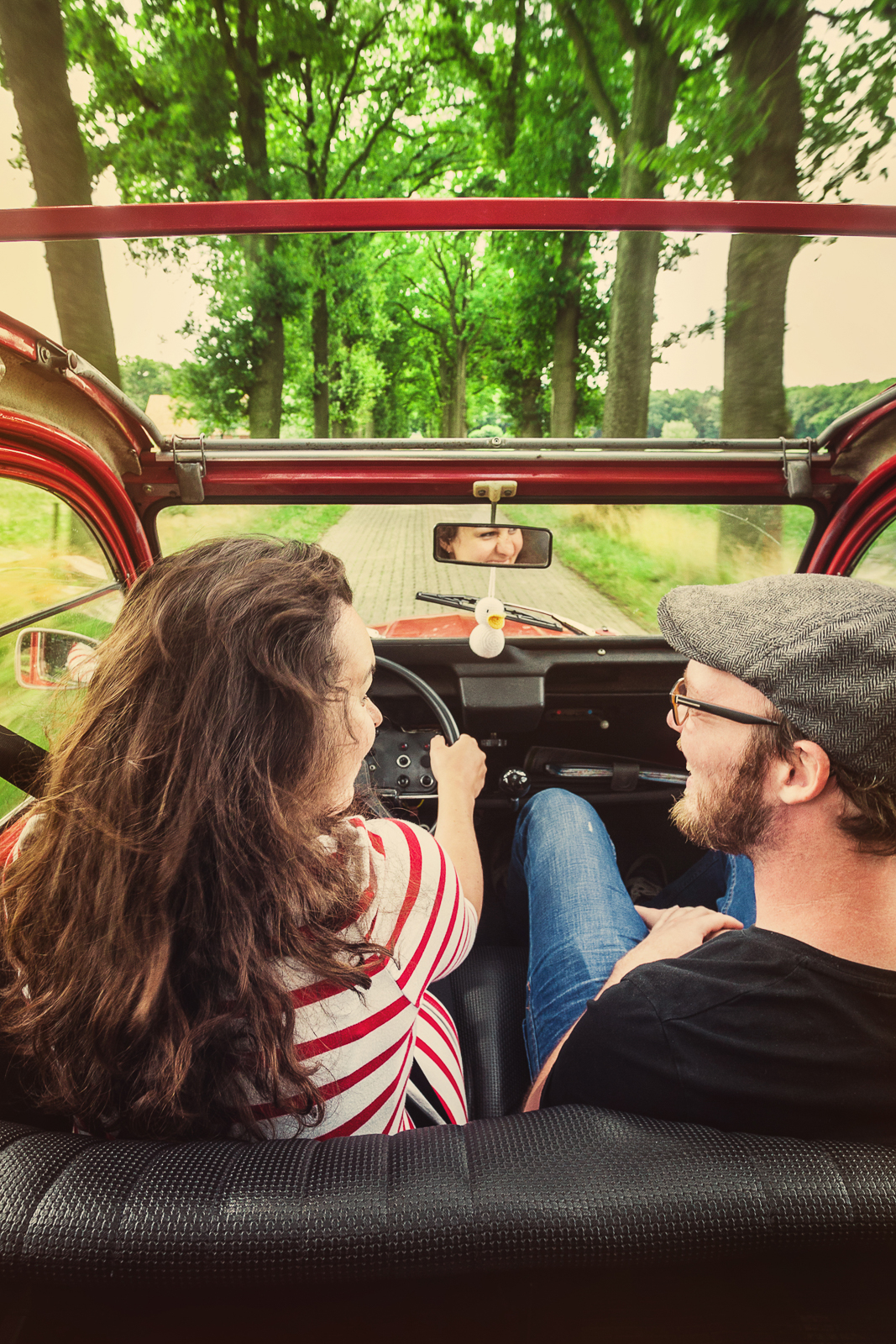 Young couple driving a simple old convertible, oldtimer, over a small country road lined with trees, smiling at eachother