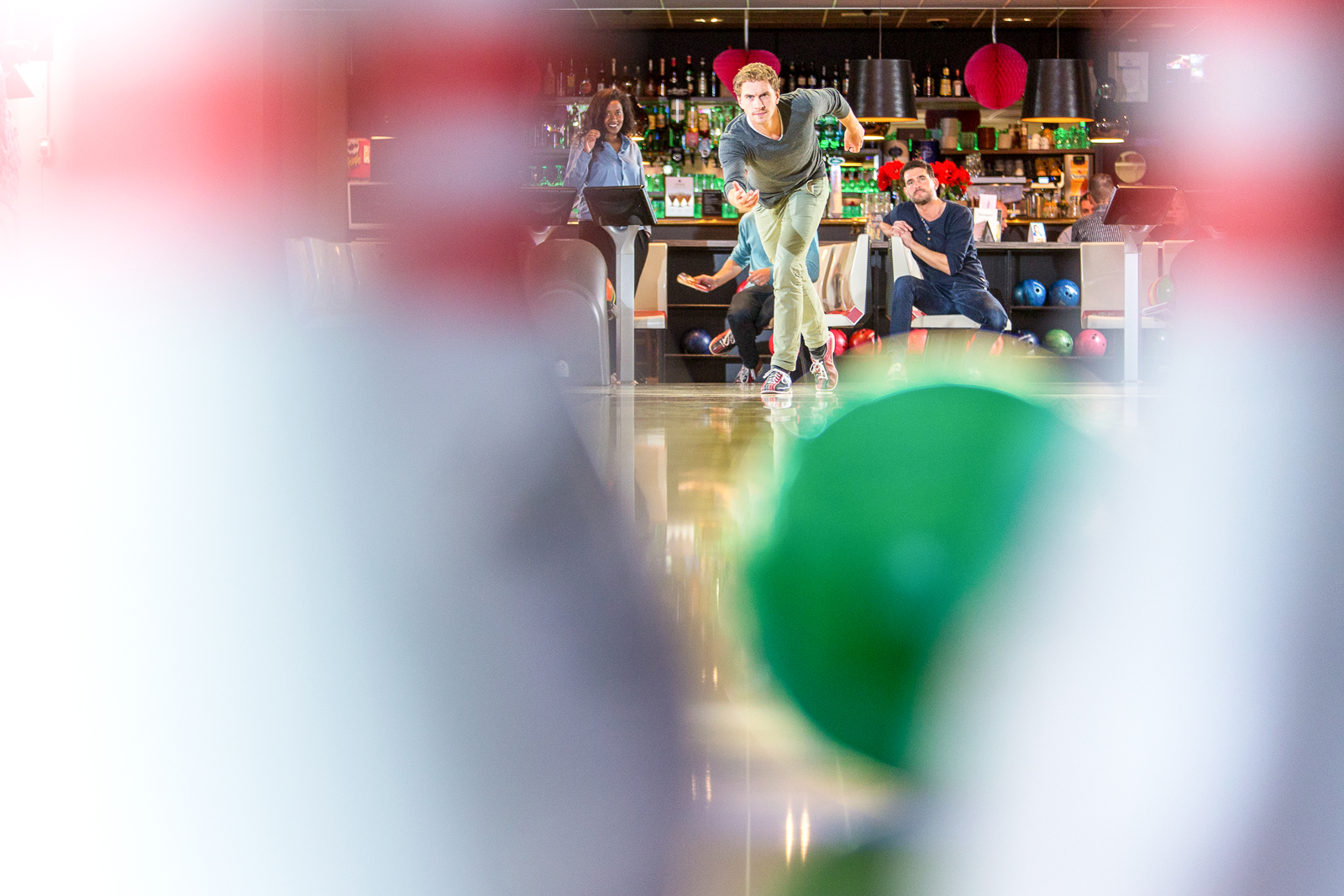 Group of friends on an active night out, bowling in a bowling alley, seen from the point of view of the pins