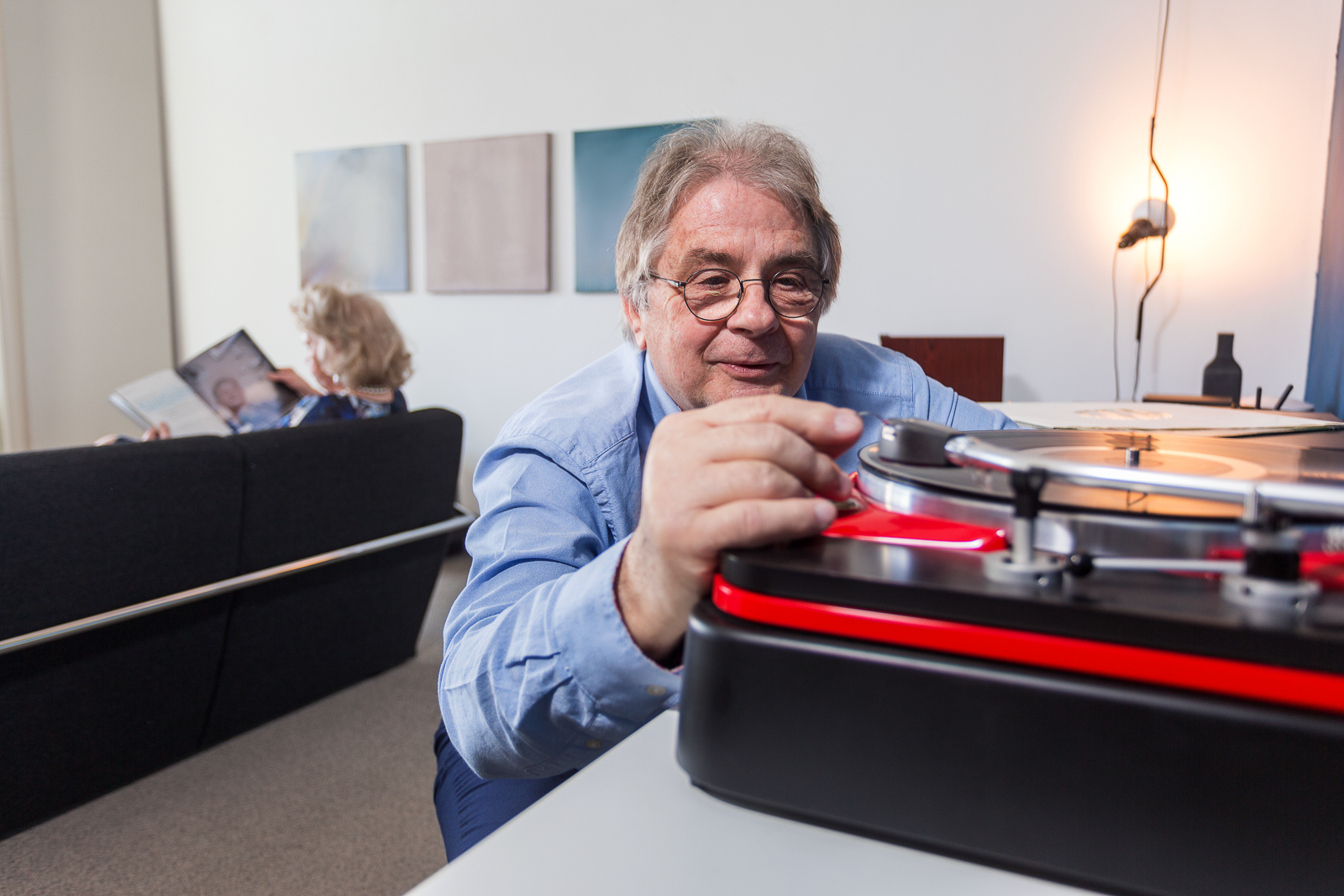 an elderly man carefully placing the needle on a vinyl record