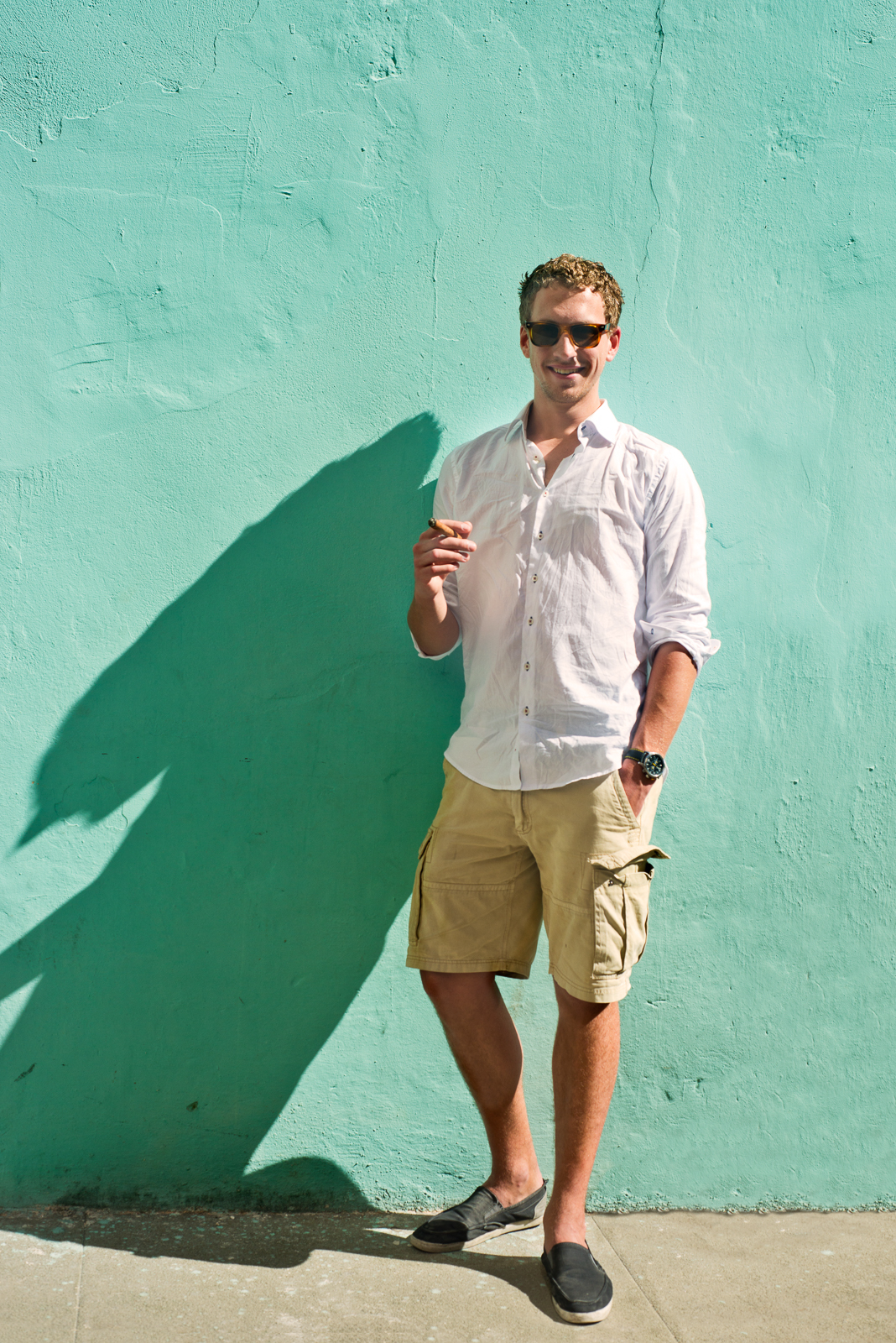 Cuban tourist with a cigar, leaning against a mint green wall