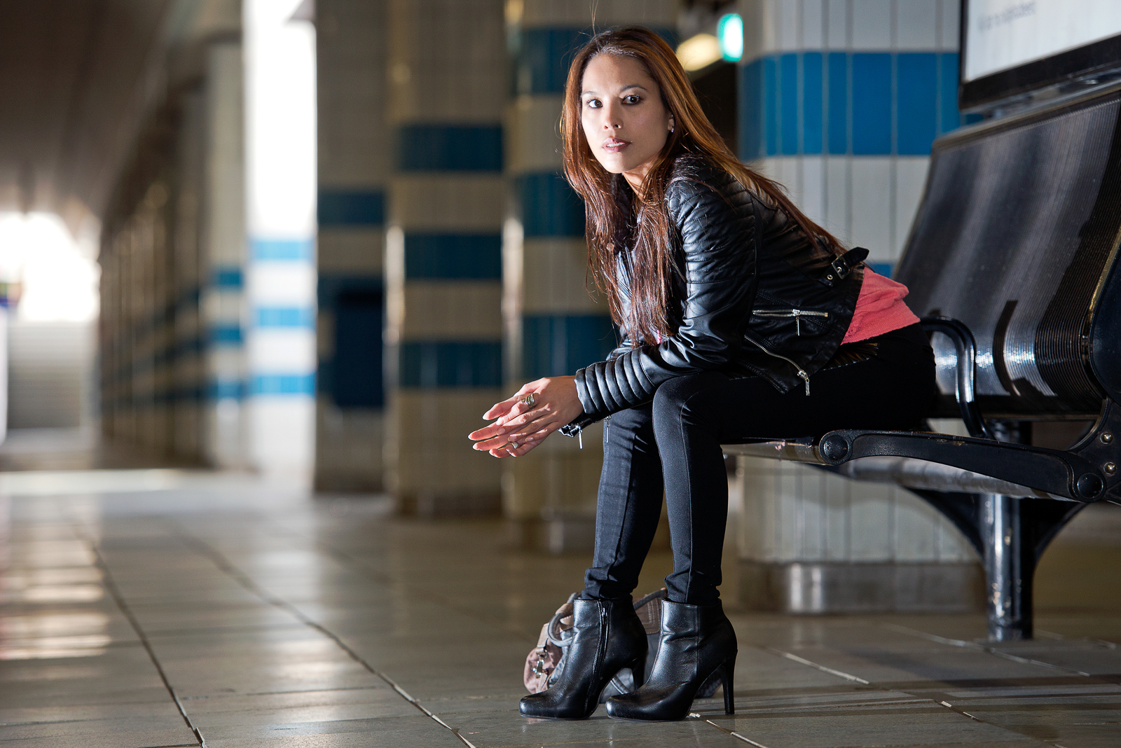 Young woman, sitting on a bench in an underground train station on the platform, wearing high heels, waiting patientely on her train to arrive
