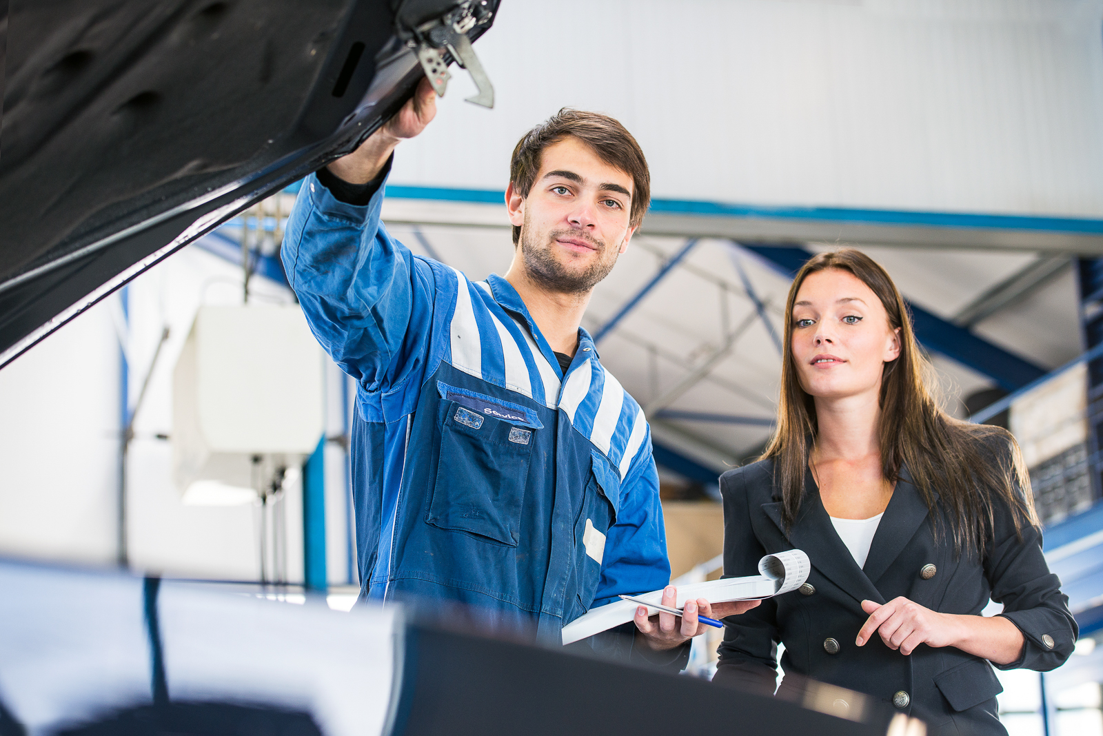 Mechanic, taking a look under the hood of a business woman's car with an order form and pen in his hand, assessing the work needed to fix her car