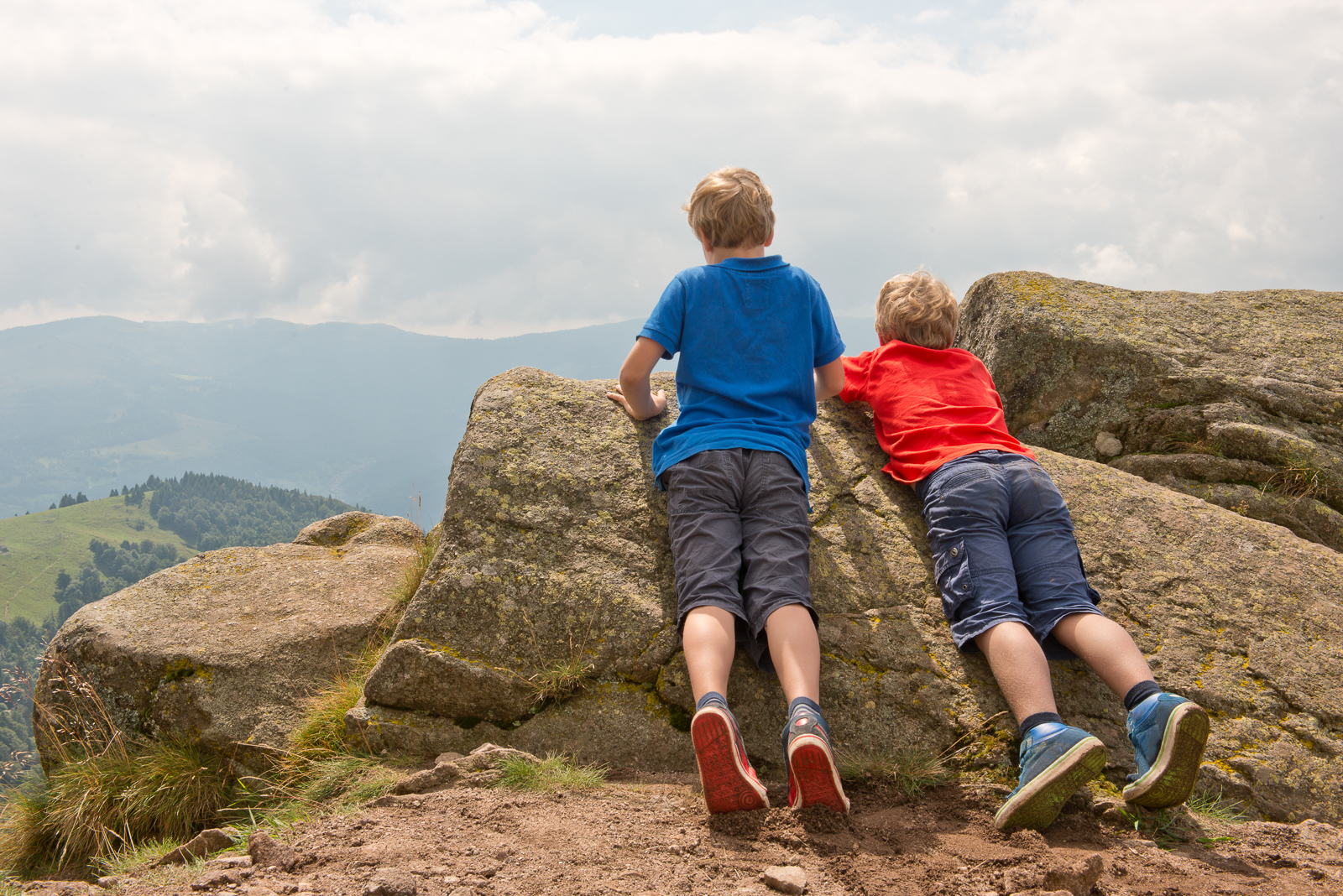 Two boys, brothers, peeking over the edge of a cliff, with their bellies on a few rocks, admiring the view