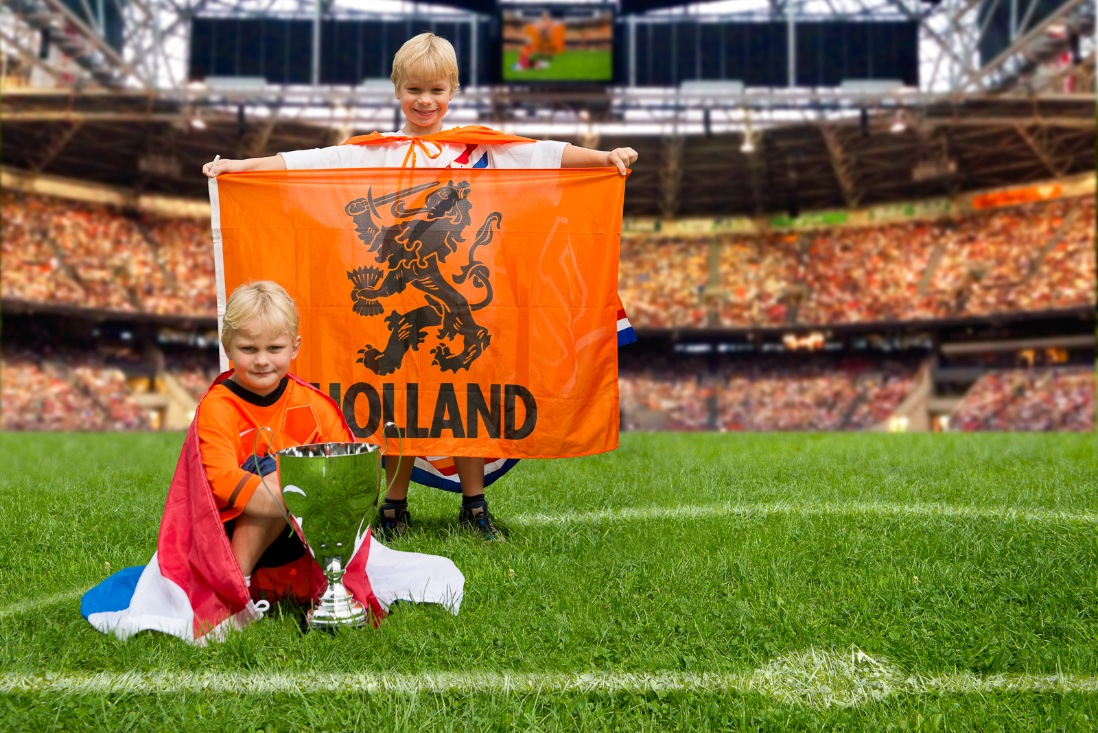 Two young boys in the middle of a huge stadium with Dutch flags and a big trophy,