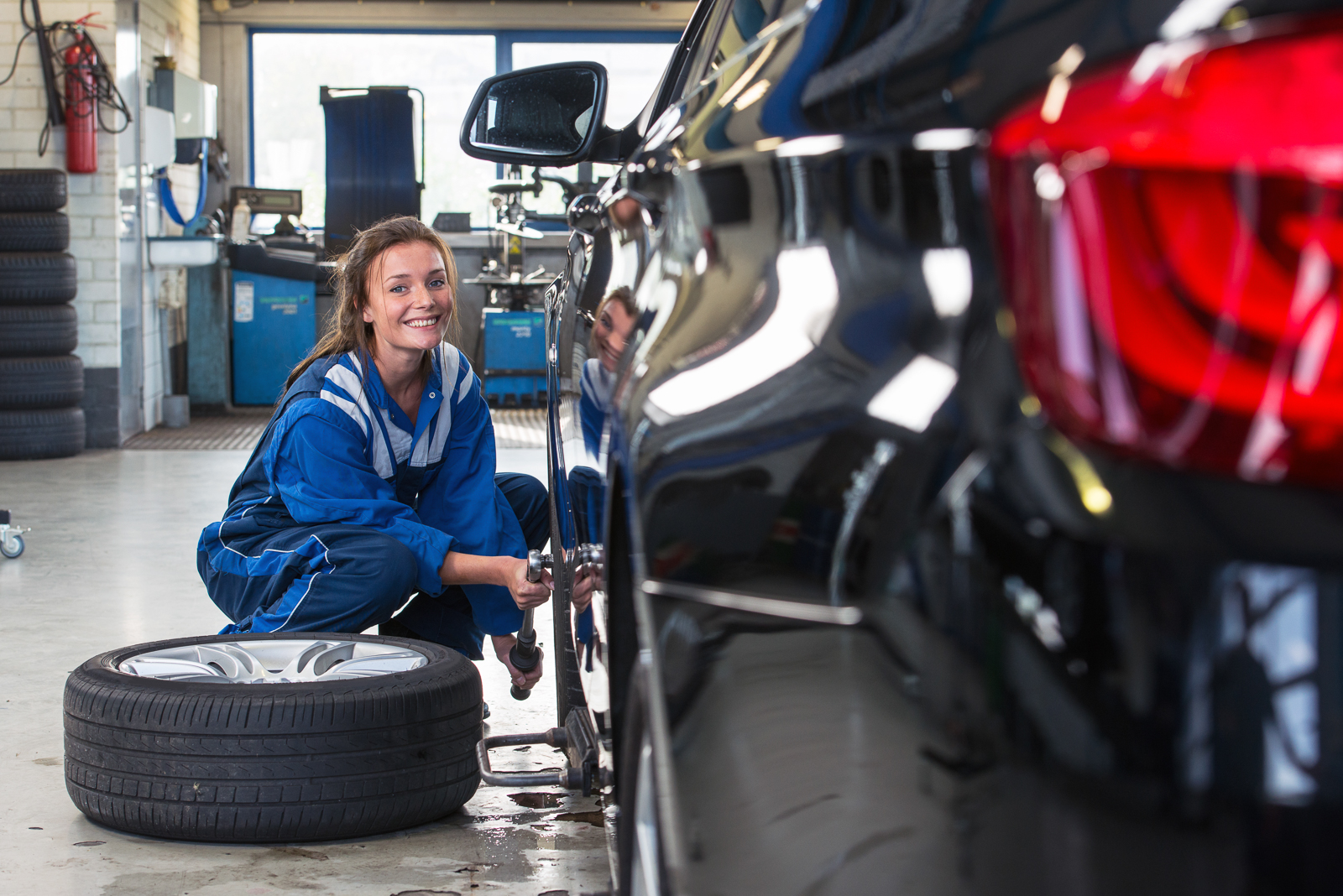 Mechanic, a young woman changing the front tire of a black sedan using a torque wrench in a tire service center garage