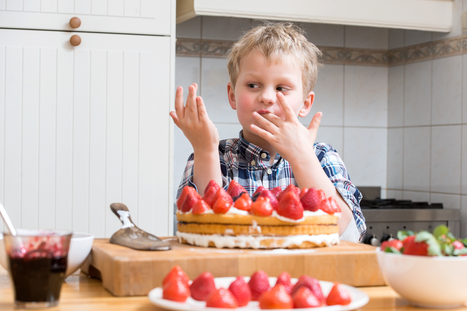 Cute boy licking his fingers with batter, behind a kitchen counter, in behind several strawberry layered cakes and pies