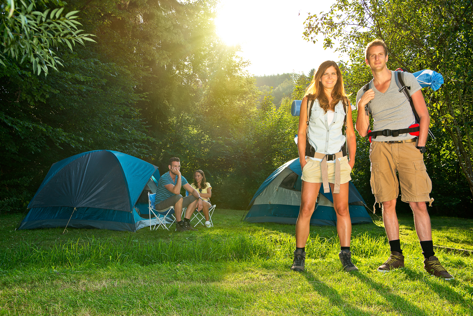 Young, attractive couple posing in front of two tents on a camp site, wearing back packs