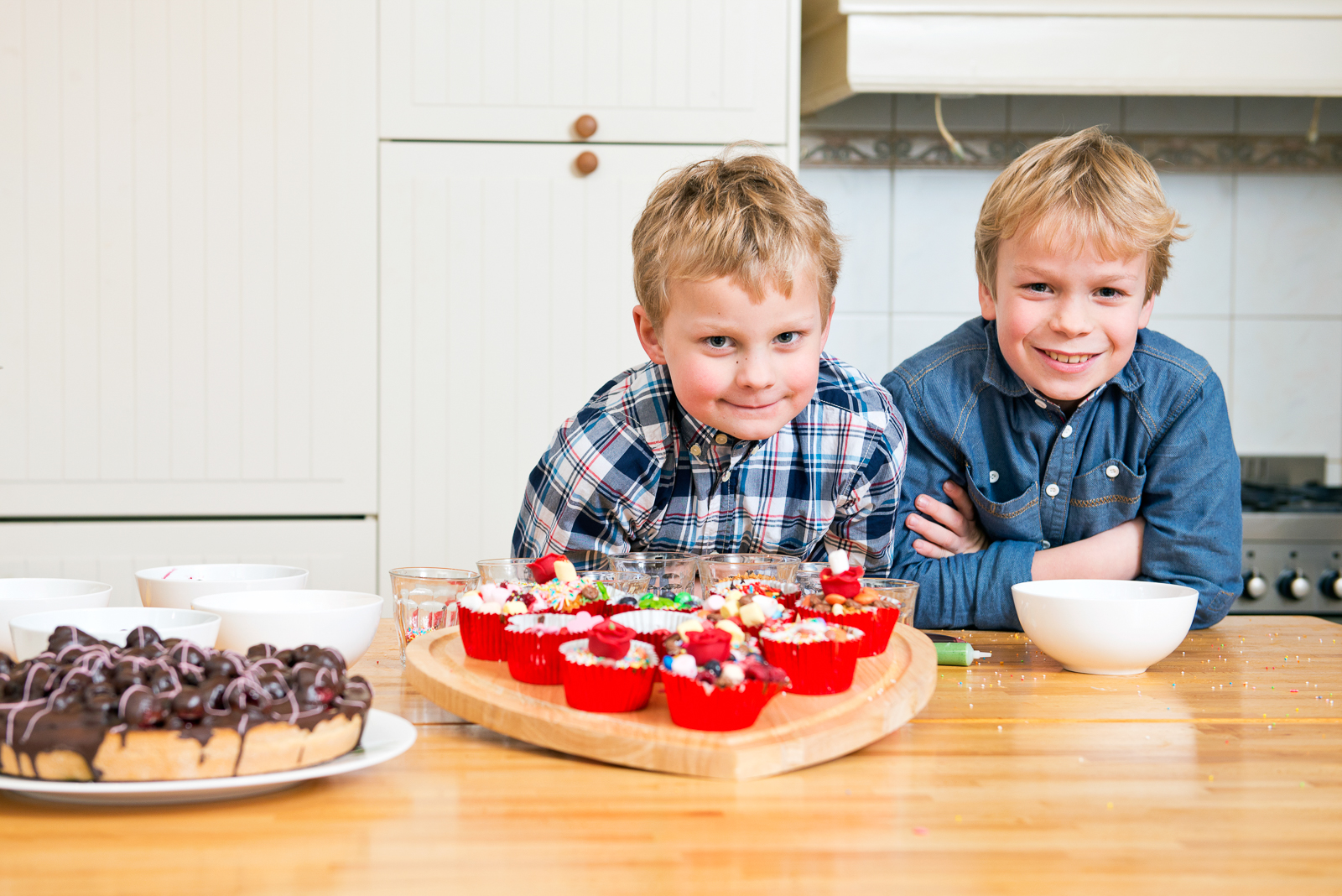 Two brothers posing in a kitchen, together in front of a heart shaped cutting board with freshly baked and decorated cupcakes