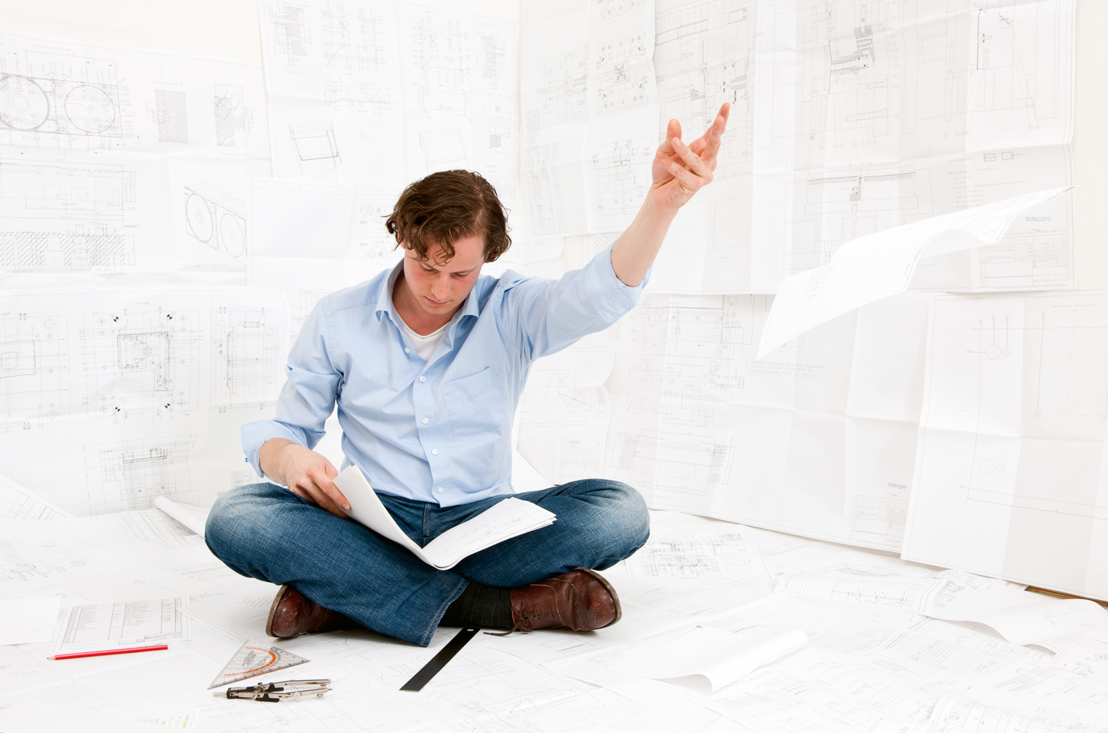 Young mechanical engineer, sitting on the floor, surrounded by complexe technical drawings of an injection mould, throwing away a drawing, whilst remaining focused on the documents in his hand