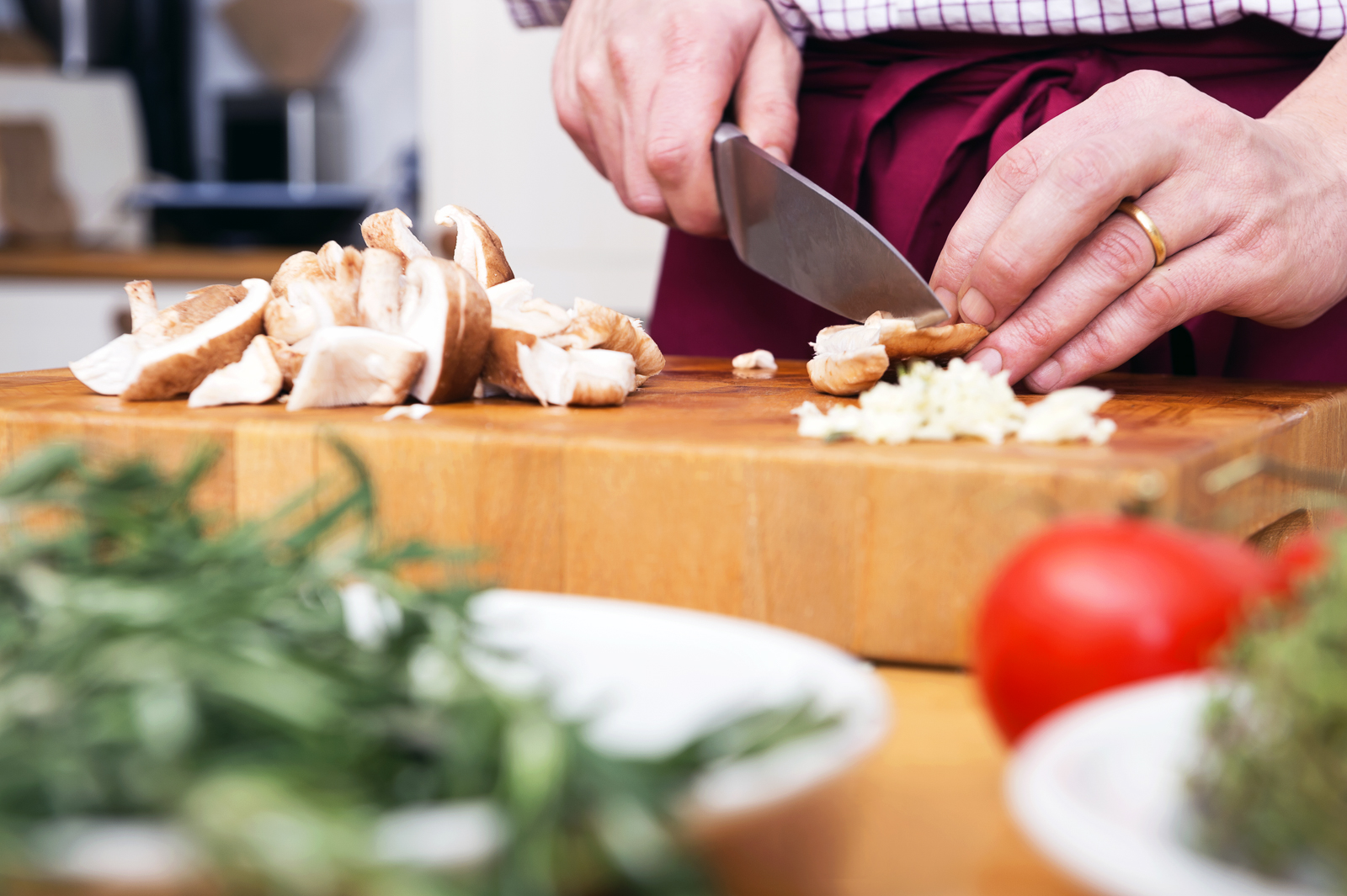 Midsection of man cutting mushrooms on chopping board