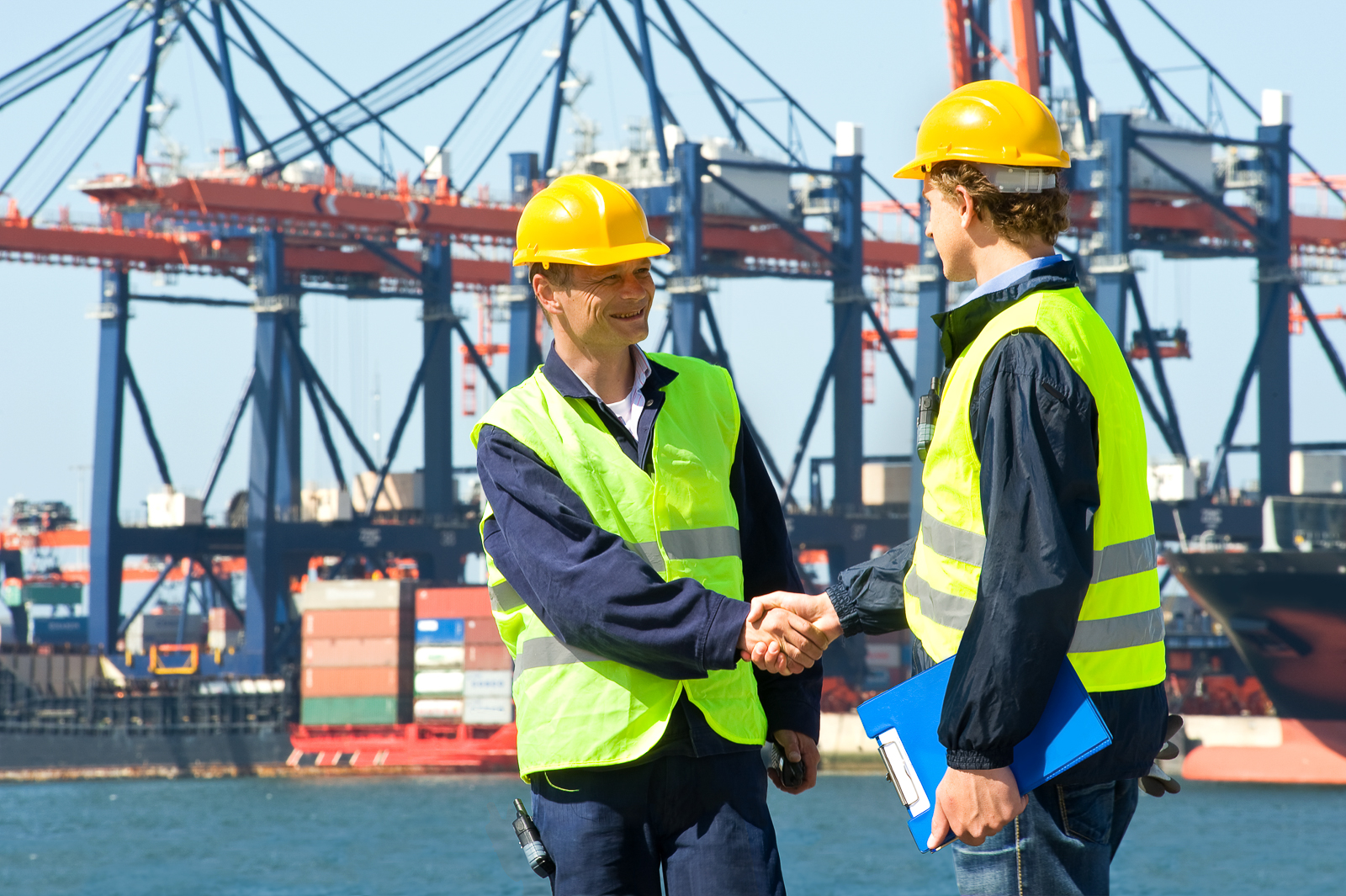 Two dockers shake hands in front of an industrial harbor with cranes and a container ship being unloaded