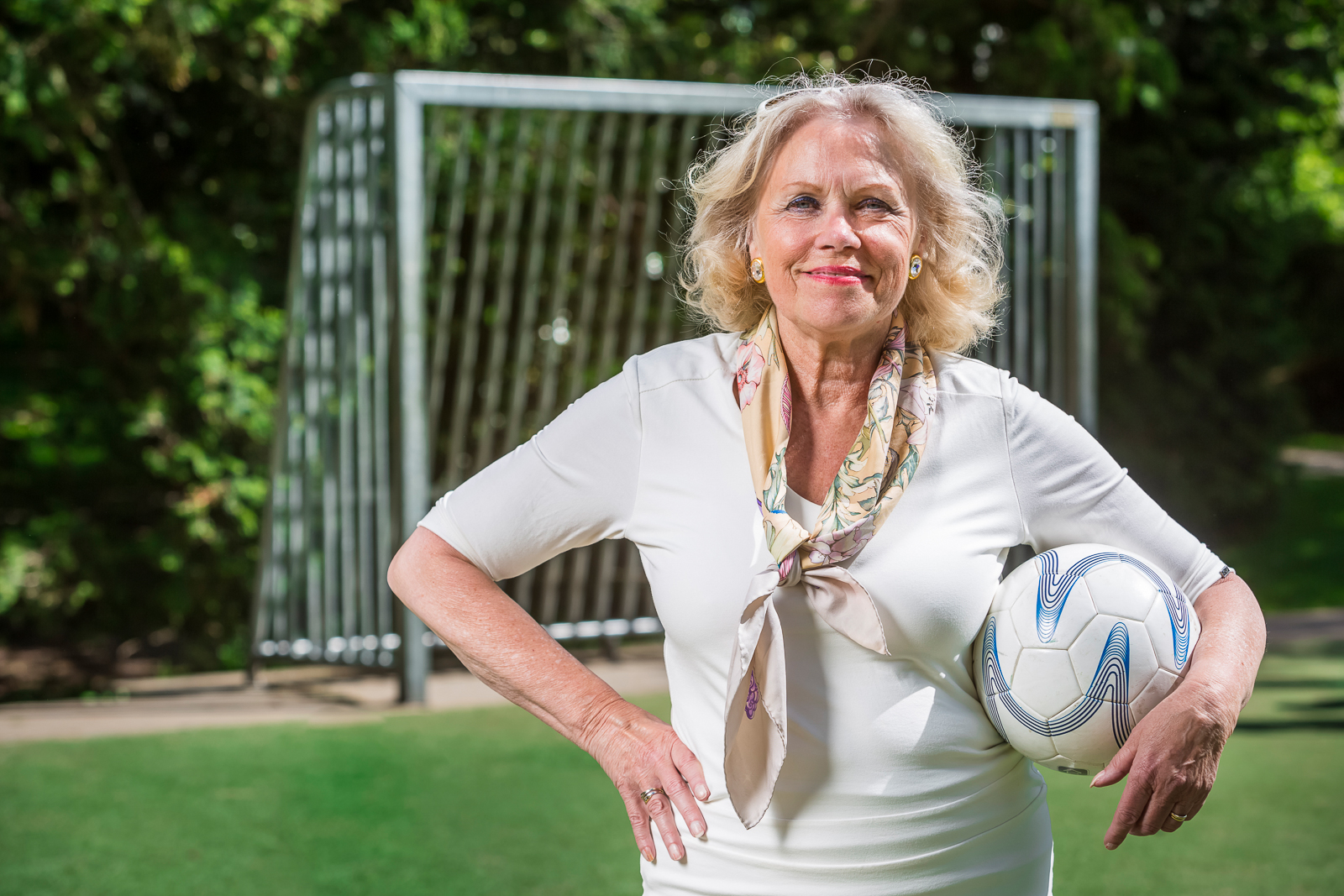 Older, retired woman, posing on a soccer pitch in a park in front of a goal, holding a ball under her arm