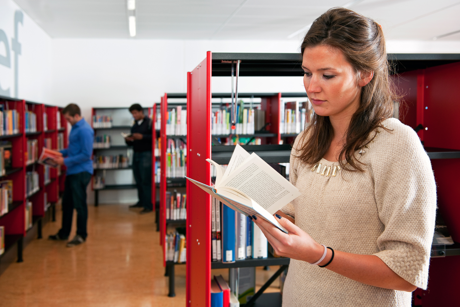 Young woman thumbing through a book in a library, with two other visitors in the background