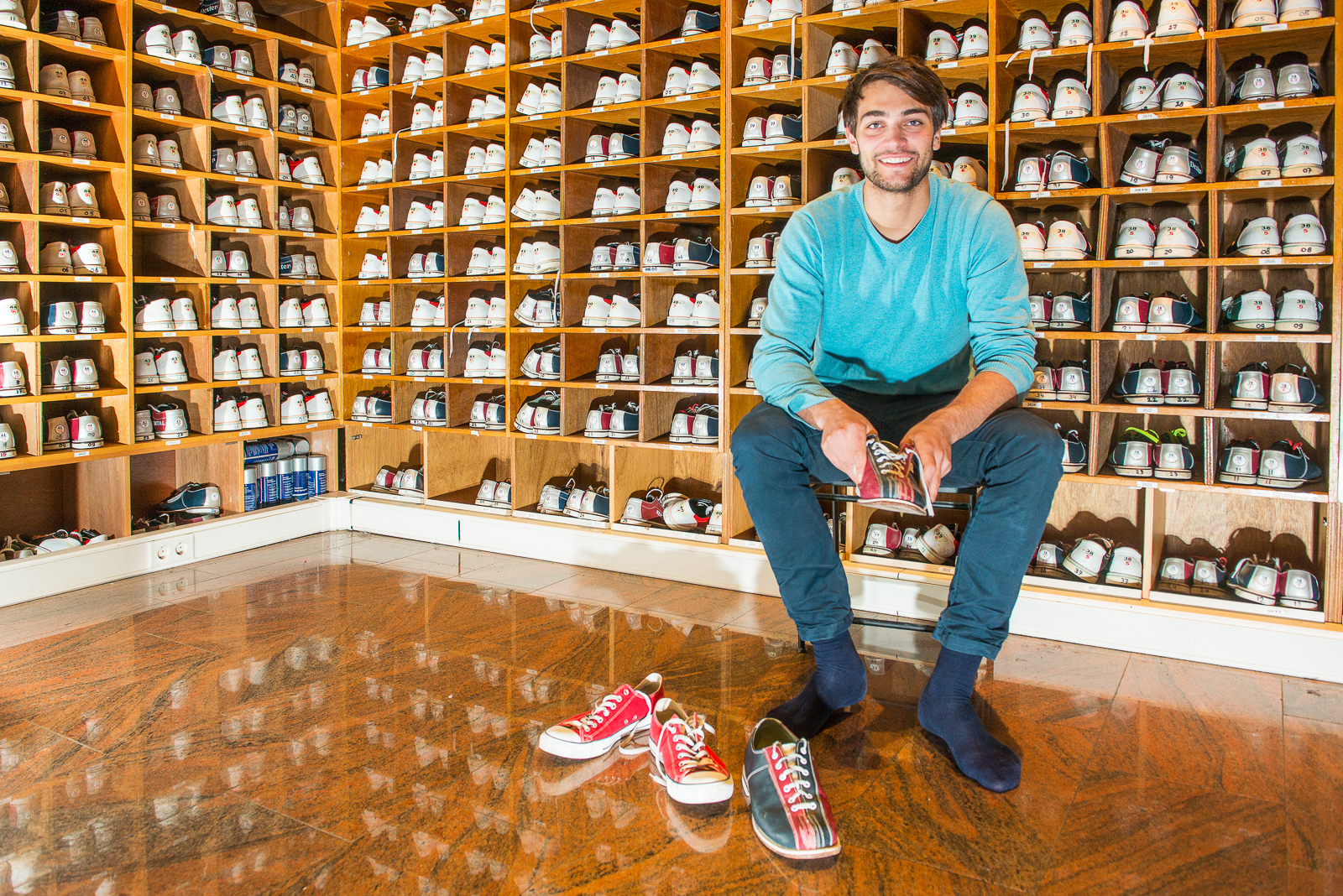 Man, sitting on a stool, surrounded by wooden shelves with various sizes of bowling shoes, trying on the sports wear, ready to go bowling