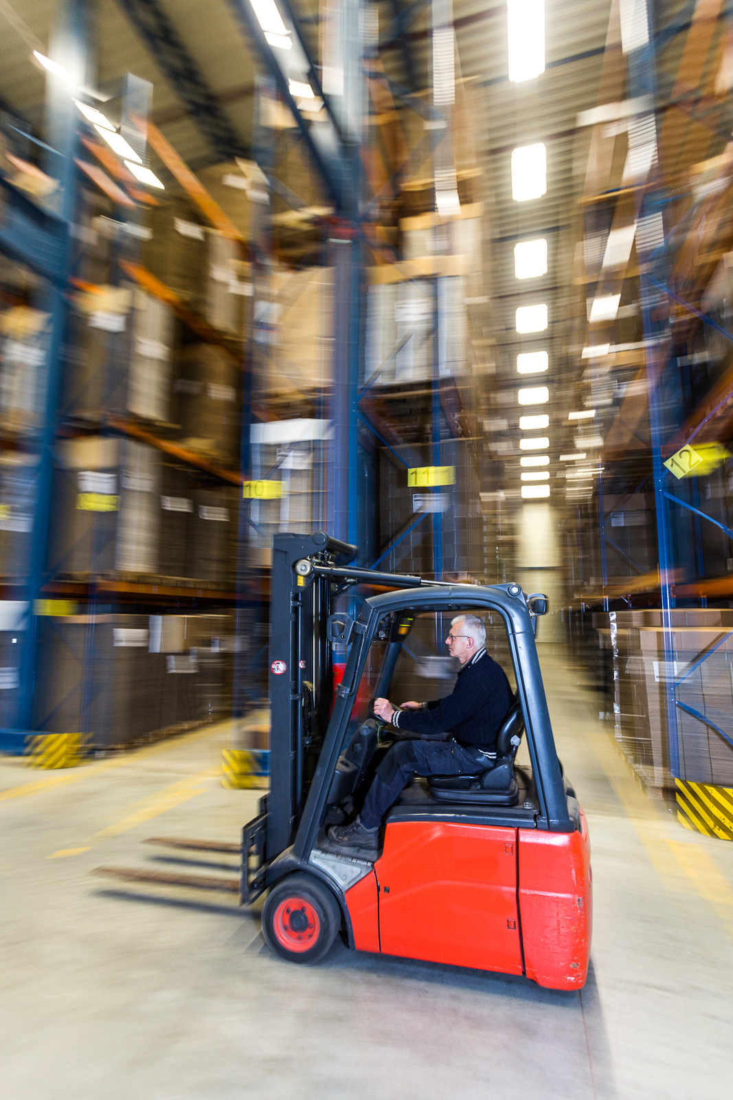 A man driving a forklift trough a warehouse